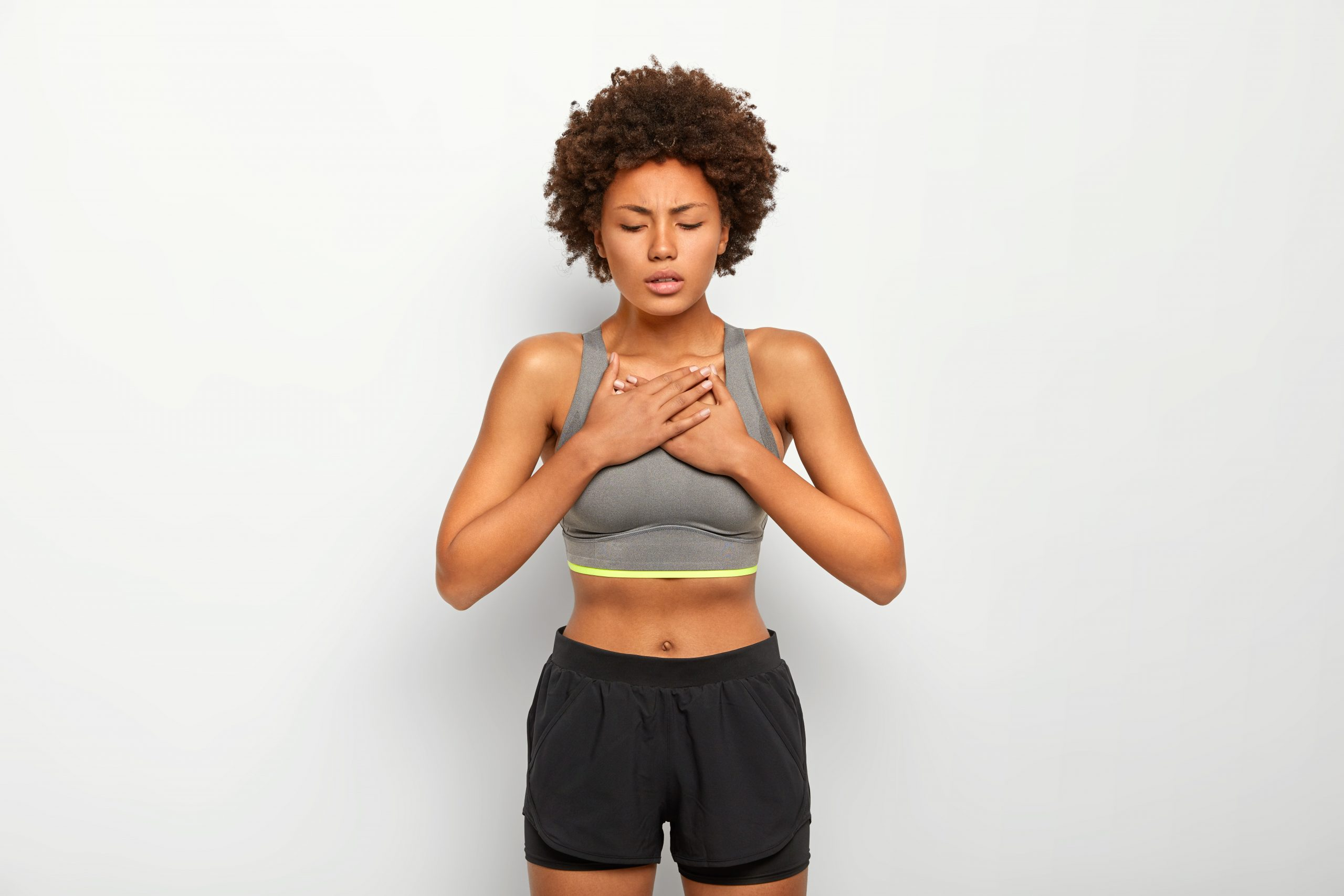 Horizontal shot of dissatisfied Afro American woman suffers from asthmatic fit, breathers deeply, has shortness of breath or dyspnoea, wears grey top and shorts, isolated over white background
