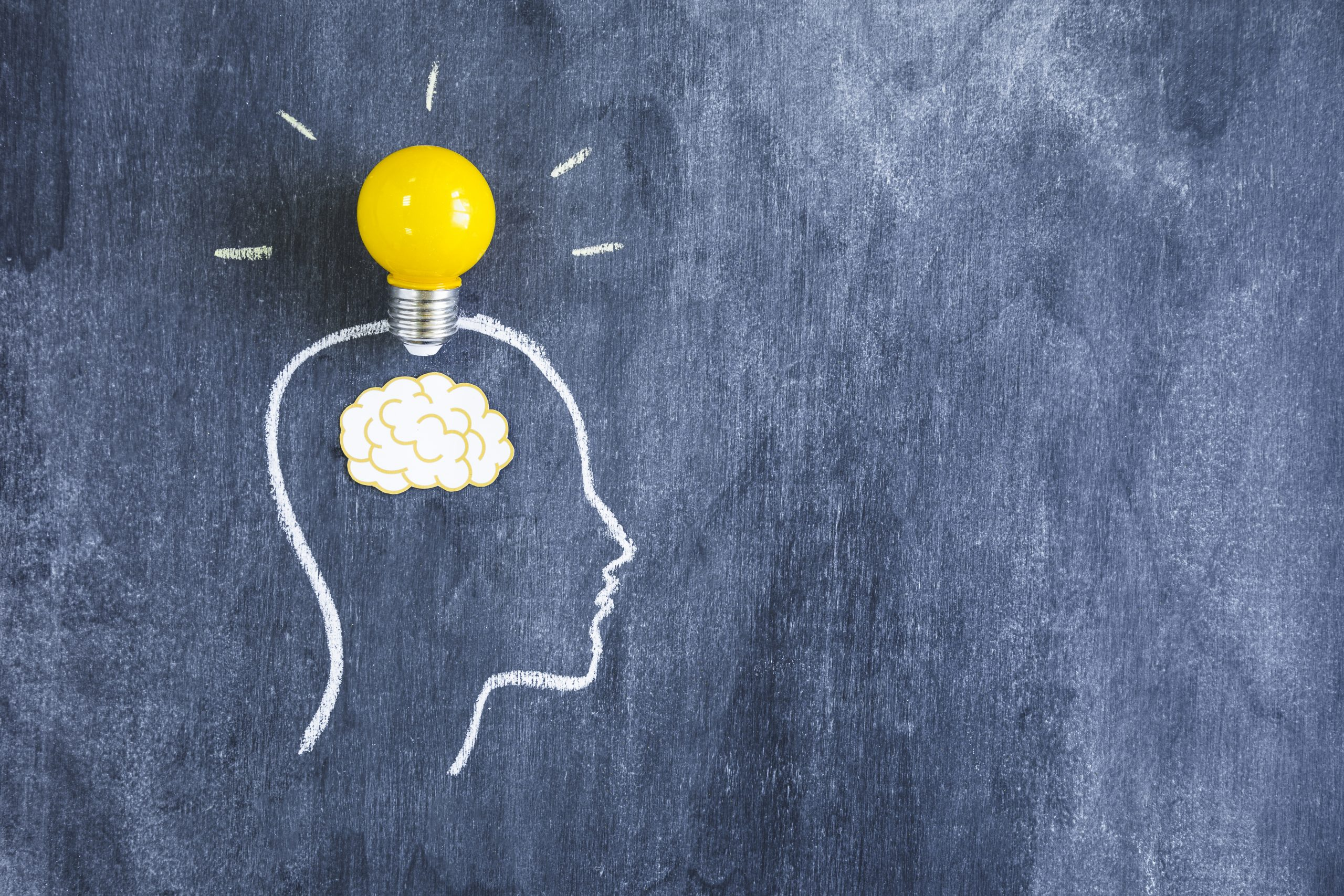 yellow-light-bulb-over-the-paper-cutout-brain-on-the-outline-face-made-with-chalk-over-the-blackboard